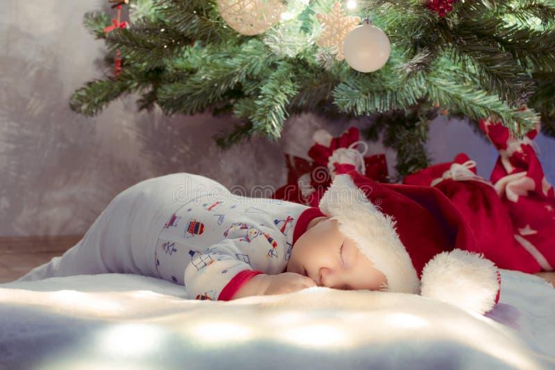 Sött nyfött behandla som ett barn pojken som sover och drömmer under julgranen royaltyfri fotografi