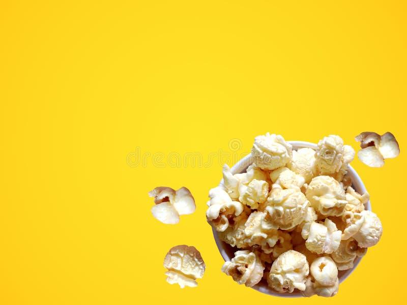 Sött popcorn med karamellanstrykning i pappers- bunke på gul bakgrund royaltyfria foton
