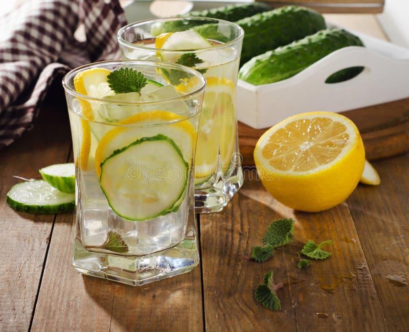 Sötvatten med citronen, mintkaramellen och gurkan på träbackgroun royaltyfria bilder