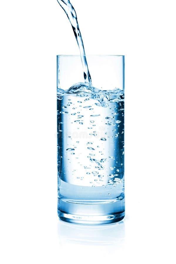Sötvatten som häller i ett exponeringsglas royaltyfri fotografi