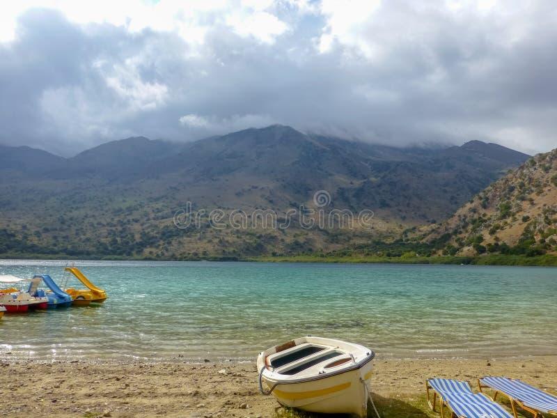 Sötvattens- sjö Kournas med rekreationutrustning i Kreta, Grekland royaltyfri fotografi
