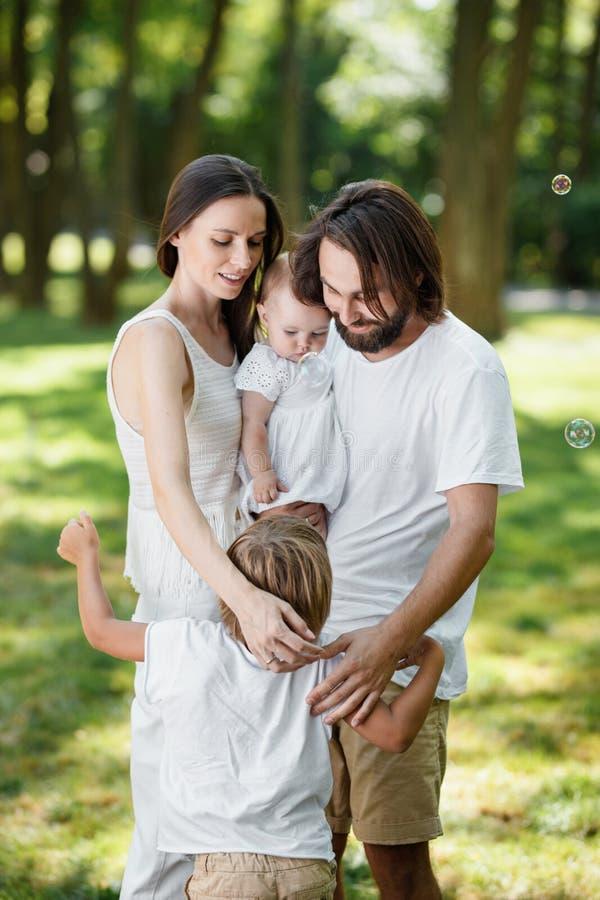 Süß hübsche Familie entspannt sich im Park Mutter und Vati halten Tochter in den Armen und umarmen ihren Sohn lizenzfreie stockbilder