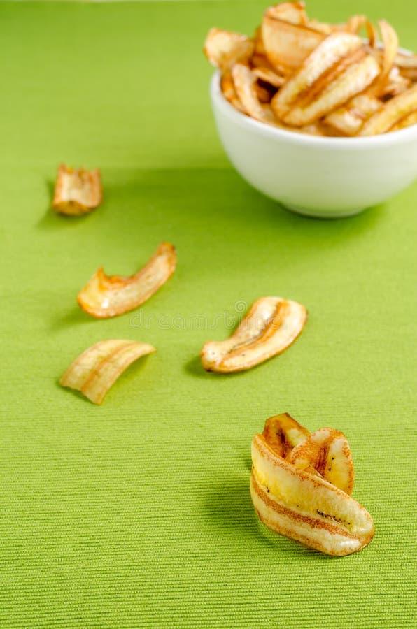 Süße Bananenchips auf grünem Tischdeckenhintergrund stockfotografie
