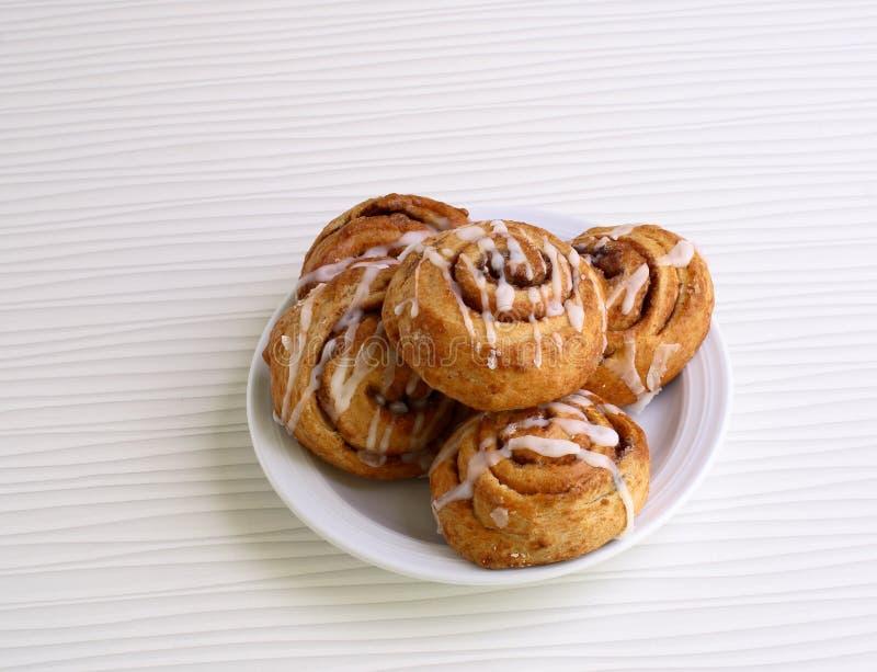 Süße Brötchen mit Zimt auf einer Platte stockfotos