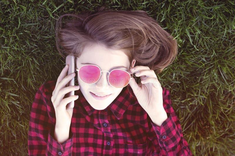 Süße Dame, die das Telefon liegt auf Gras verwendet lizenzfreie stockfotos