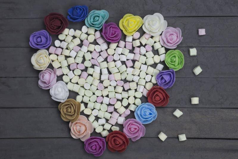 Süße Eibische in der Herzform verziert mit Blumen auf hölzernem Hintergrund getrennt auf weißem, selektivem Fokus stockfotos