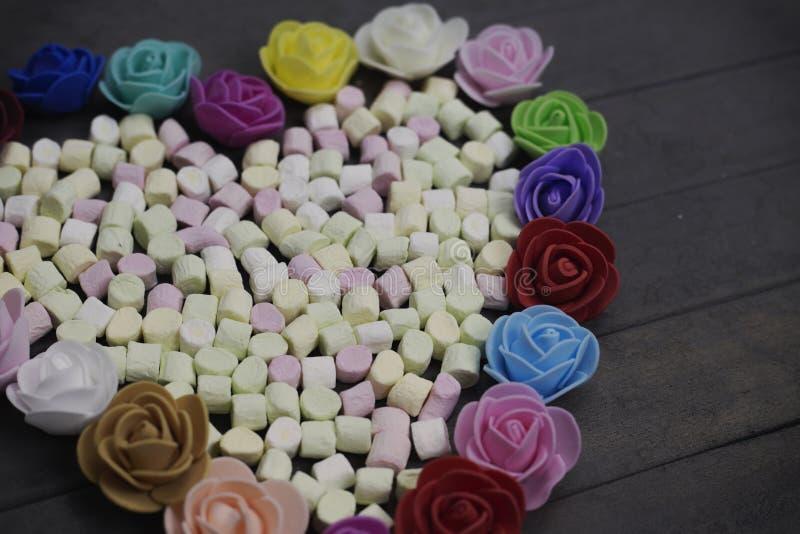 Süße Eibische in der Herzform verziert mit Blumen auf hölzernem Hintergrund getrennt auf weißem, selektivem Fokus stockfotografie
