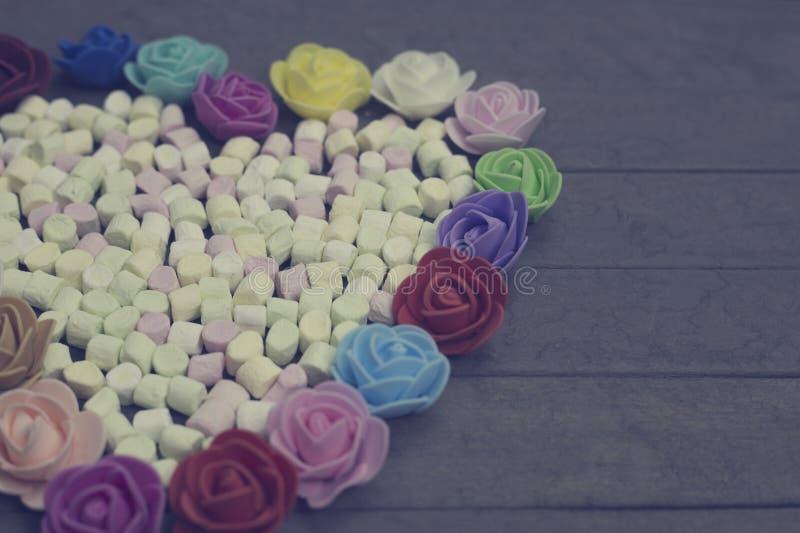 Süße Eibische in der Herzform verziert mit Blumen auf hölzernem Hintergrund getrennt auf weißem, selektivem Fokus lizenzfreies stockfoto