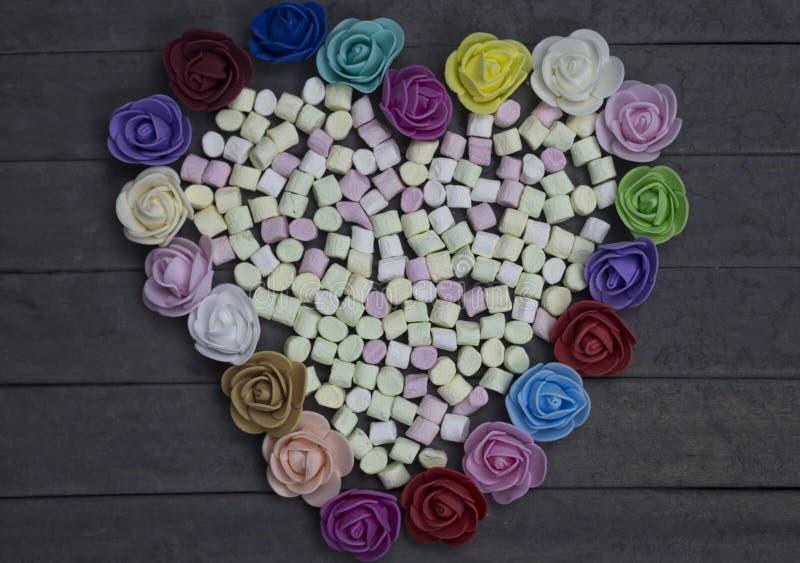 Süße Eibische in der Herzform verziert mit Blumen auf hölzernem Hintergrund getrennt auf weißem, selektivem Fokus lizenzfreies stockbild
