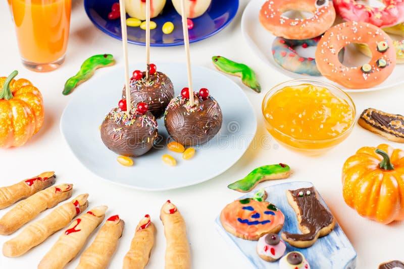 Süße Festlichkeiten Halloweens, Parteilebensmittelkonzept Furchtsame Plätzchen, Monsterkekse und Früchte auf weißem Hintergrund lizenzfreies stockbild