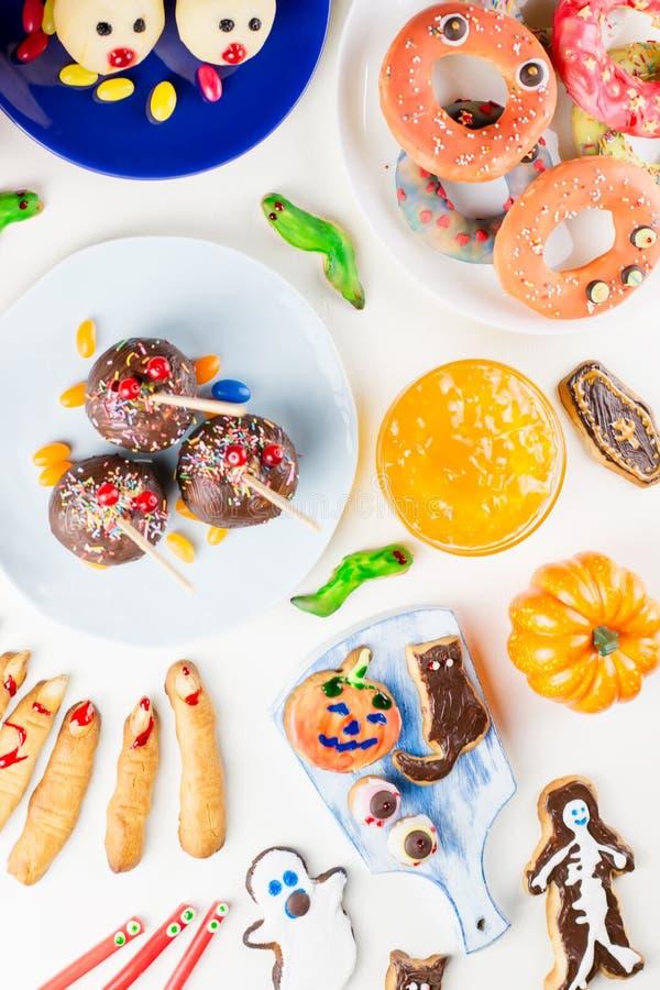Süße Festlichkeiten Halloweens, Parteilebensmittelkonzept Furchtsame Plätzchen, Monsterkekse und Früchte auf weißem Hintergrund lizenzfreies stockfoto