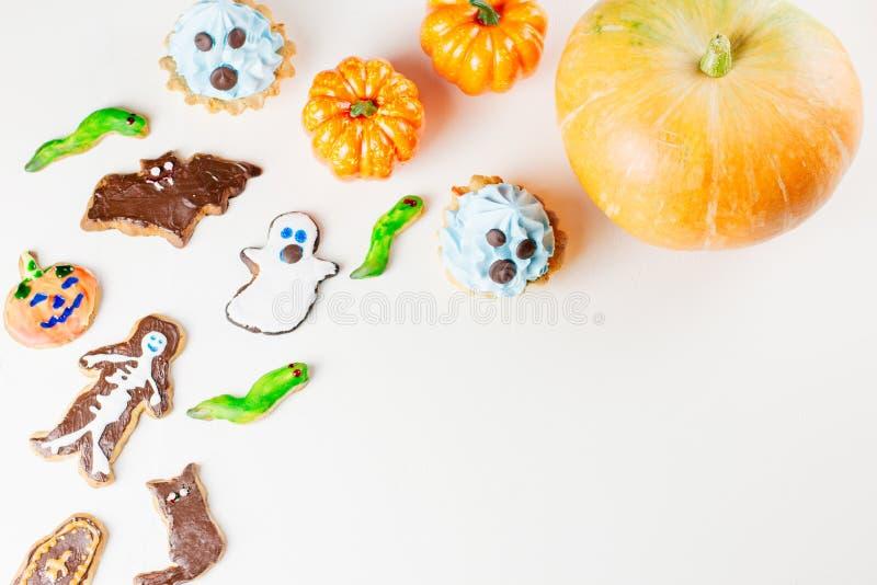 Süße Festlichkeiten Halloweens, Parteilebensmittelkonzept Furchtsame Plätzchen, Monsterkekse und Früchte auf weißem Hintergrund stockbild