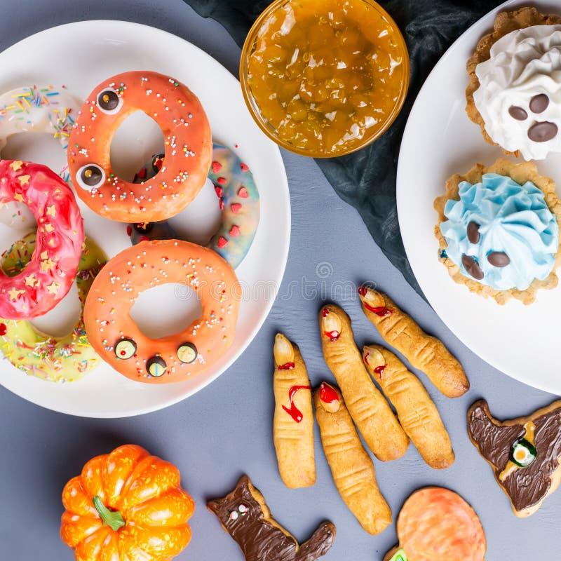 Süße Festlichkeiten Halloweens, Parteilebensmittelkonzept Furchtsame Plätzchen und Äpfel eingetaucht in Schokolade lizenzfreies stockfoto