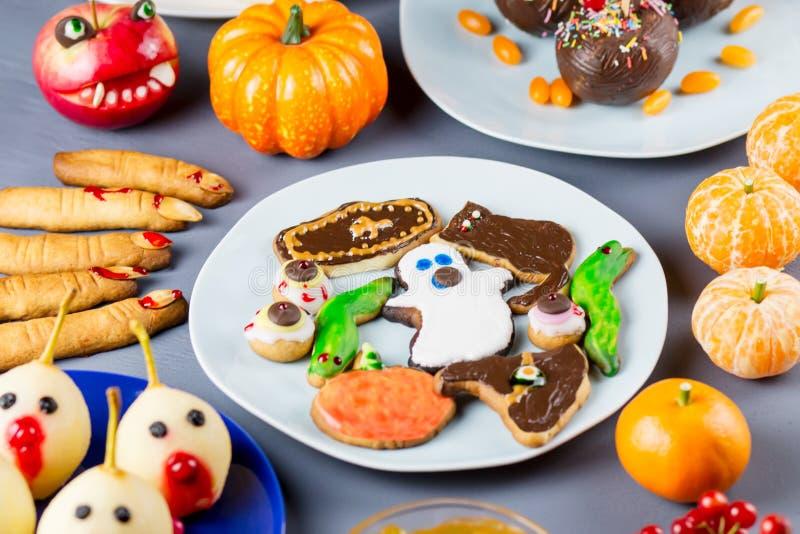 Süße Festlichkeiten Halloweens, Parteilebensmittelkonzept Furchtsame Plätzchen und Äpfel eingetaucht in Schokolade stockfoto