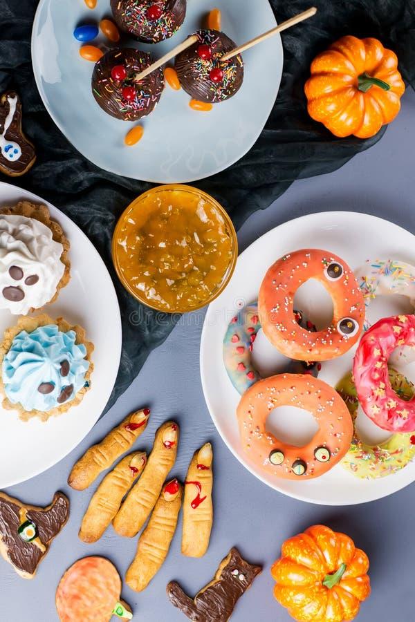Süße Festlichkeiten Halloweens, Parteilebensmittelkonzept Furchtsame Plätzchen und Äpfel eingetaucht in Schokolade lizenzfreies stockbild