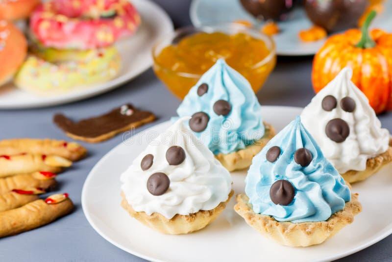 Süße Festlichkeiten Halloweens, Parteilebensmittelkonzept Weiße und blaue kleine Kuchen mit Gesichtern schließen oben lizenzfreies stockfoto