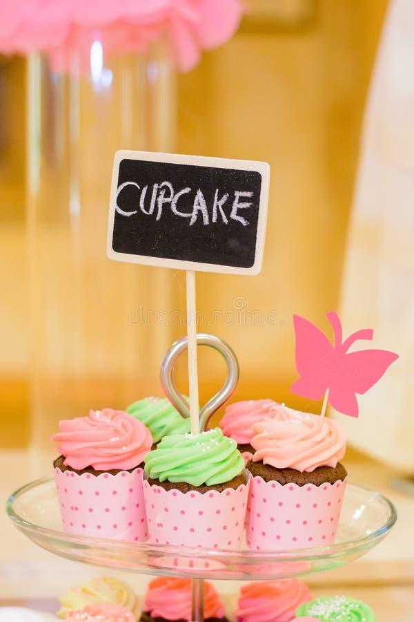 Süße geschmackvolle farbige kleine Kuchen mit unscharfem Hintergrund auf einem Glas stockbild