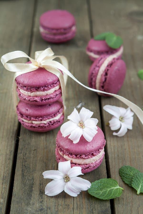 Süße hochrote französische Makronen mit Hyazinthenblumen und -minze auf dunklem hölzernem Hintergrund stockbilder