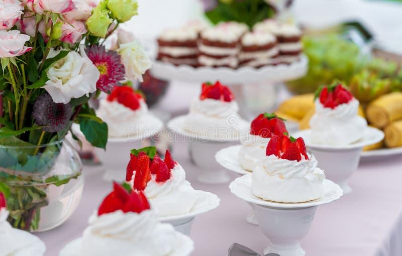 Süße Hochzeitstorten mit Erdbeere auf Spitze und Früchten im Hintergrund stockfoto