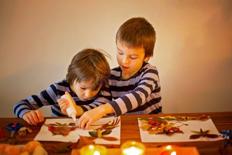 Süße Kinder, die Jungen, zutreffend verlässt mit Kleber beim Handeln von Kunst stockfoto