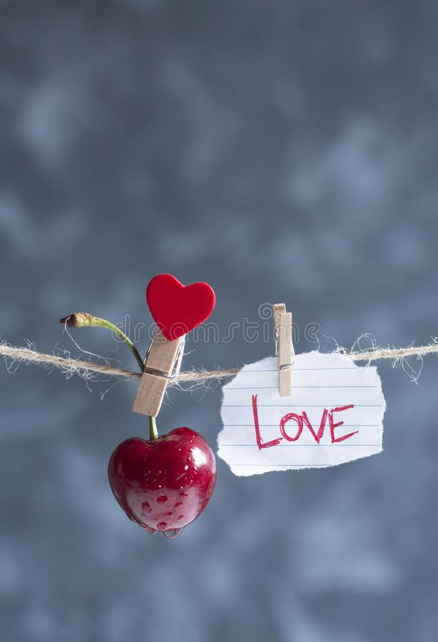 Süße Kirsche und Fetzen des Papiers mit einem Wort lieben auf einem Seil lizenzfreie stockfotos