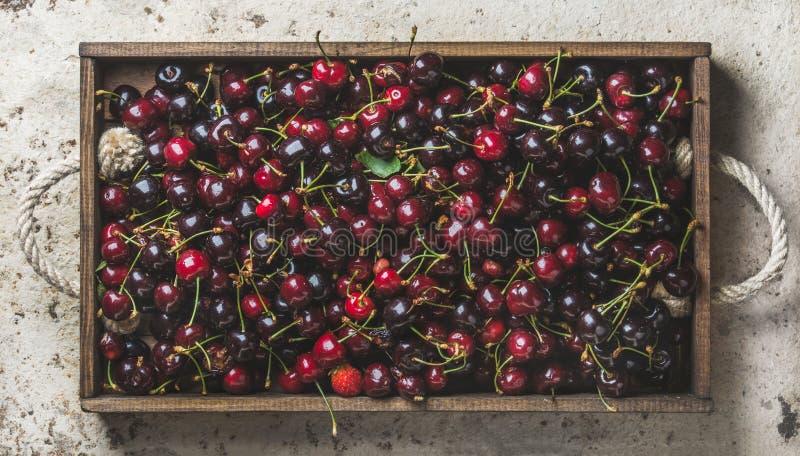 Süße Kirschen im rustikalen hölzernen Behälter über Leichtbetonhintergrund stockfotos