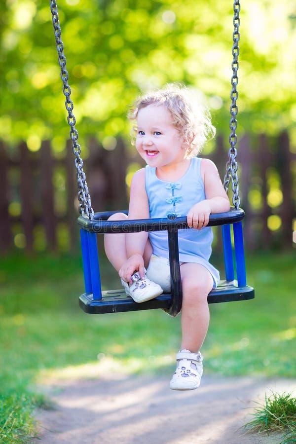 Süße lachende Kleinkindmädchenschwingfahrt auf Spielplatz stockfotos