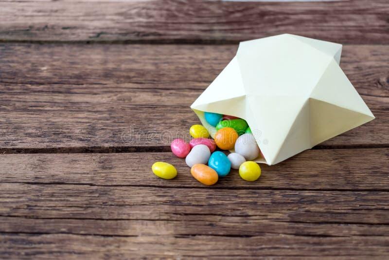 Süße mehrfarbige Süßigkeitspillen in der Papiergeschenkbox in Form lizenzfreies stockbild
