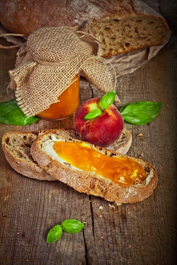 Süße Pfirsichmarmelade auf Brot lizenzfreies stockfoto