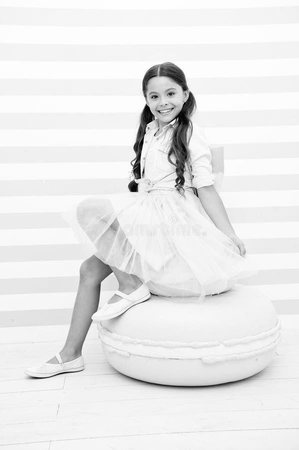 Süße Prinzessin Entzückendes lächelndes Gesicht des Kindermädchens, das auf nettem süßem Makronenpuff aufwirft Abnutzung des Kind stockbilder