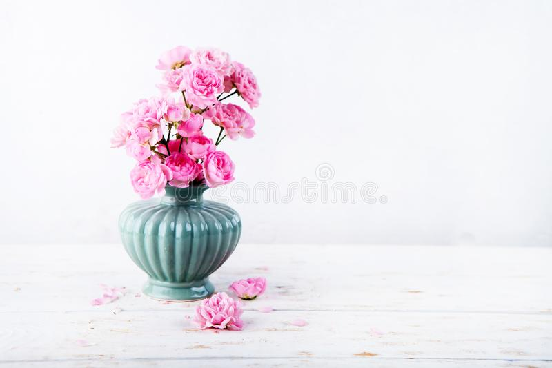 Süße rosa Rosen blüht in den Vasen auf Weiß gemaltem hölzernem Hintergrund gegen weiße Wand Selektiver Fokus Platz für Text Geton lizenzfreie stockbilder