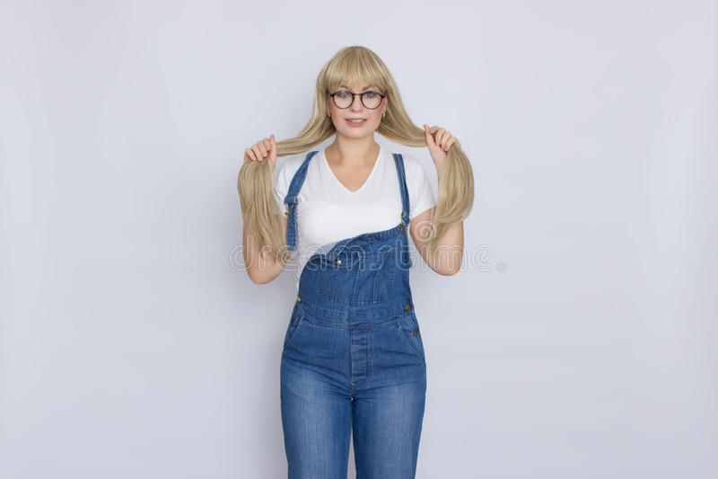 Süße schöne blonde Frau mit dem langen Haar im Blue Jeans-Overall und den Gläsern über grauem Hintergrund lizenzfreies stockfoto
