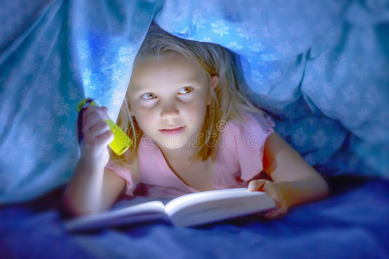 Süße schöne und recht kleine blonde alte Lügen des Kindmädchens 6 bis 8 Jahre unter Bettabdeckungs-Lesebuch in der Dunkelheit mit lizenzfreies stockbild