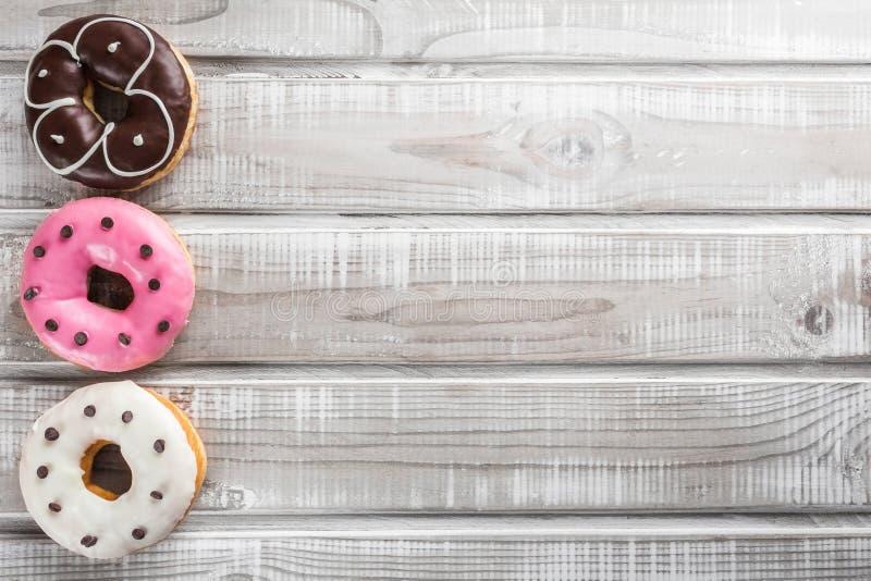 Süße Schaumgummiringe auf einer alten Draufsicht des Holztischs stockbild