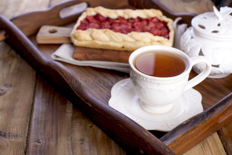 Süße selbst gemachte Torte für Frühstück und eine Schale schwarzen Tee, auf einem krchovom hölzernen Behälter Freier Raum für Tex lizenzfreie stockbilder