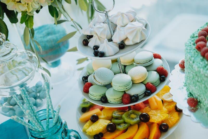 Süße Tabelle mit bunten Makronen, Früchten und Kuchen lizenzfreies stockbild