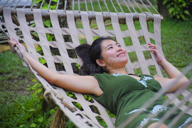 Süße und entspannte asiatische Chinesin auf ihrem 20s, das grünen Sommer trägt, kleiden liegendes durchdachtes nachdenkliches und stockfoto