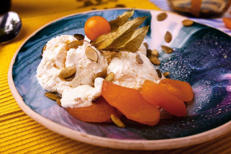 Süße weiße Eiscreme mit Physalis und getrockneten Aprikosen auf einem Gelb verwischte Hintergrund Auffrischung und kalte Nachtisc lizenzfreies stockfoto