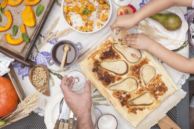 Süßer, gebackener Kürbis und Torte mit Birne Herbstabendessen für die ganze Familie Kind-` s Hände und Männer im Rahmen Kopieren  stockfoto
