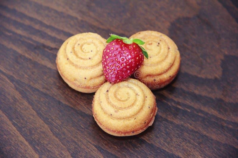 Süßer gelber Keks backt Oberteile mit Erdbeerdekor zusammen lizenzfreies stockbild