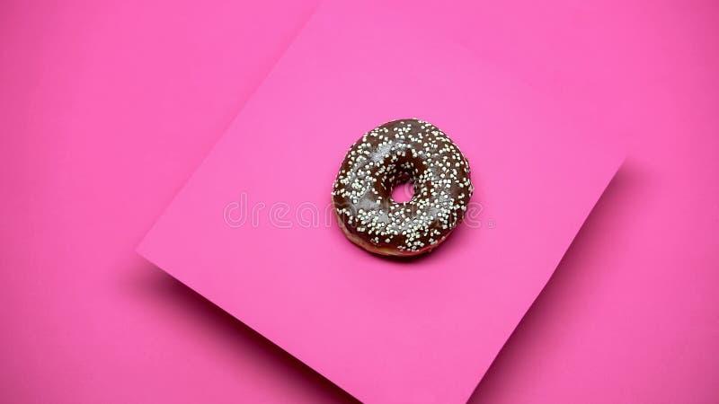 Süßer glasig-glänzender Donut auf rosa Hintergrund, kulinarische Künste, geschmackvolle Bäckerei, Makroschuß stockfotografie