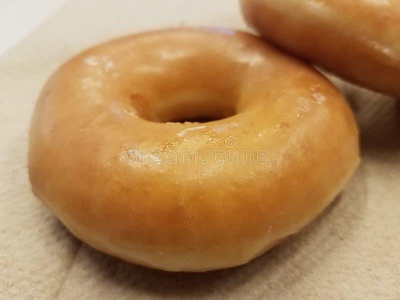 Süßer glasig-glänzender Zuckerdonut auf braunem Papierhandtuch stockbild