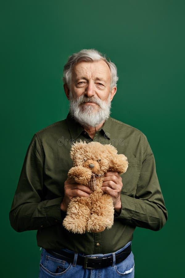 Süßer hübscher älterer Herr, der einen Teddybären lokalisiert auf grünem Hintergrund hält stockfotos