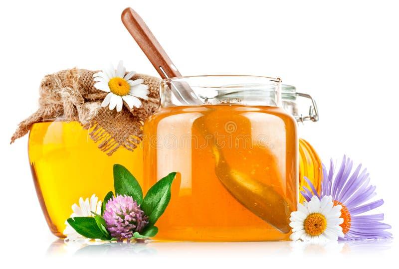 Süßer Honig im Glasglas mit Löffel und Blumen stockfotografie