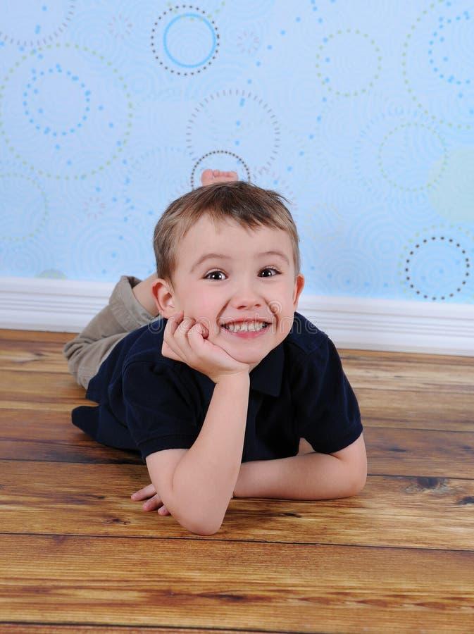 Süßer kleiner Junge, der auf Fußboden mit der Hand auf Kinn legt lizenzfreies stockfoto