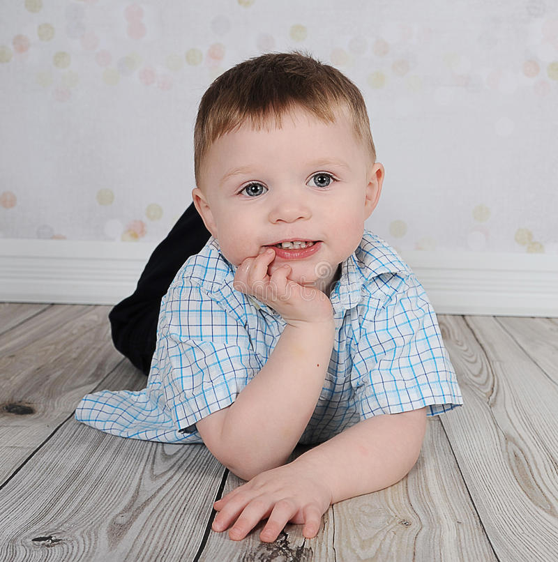 Süßer kleiner Junge, der für Kamera aufwirft stockbild