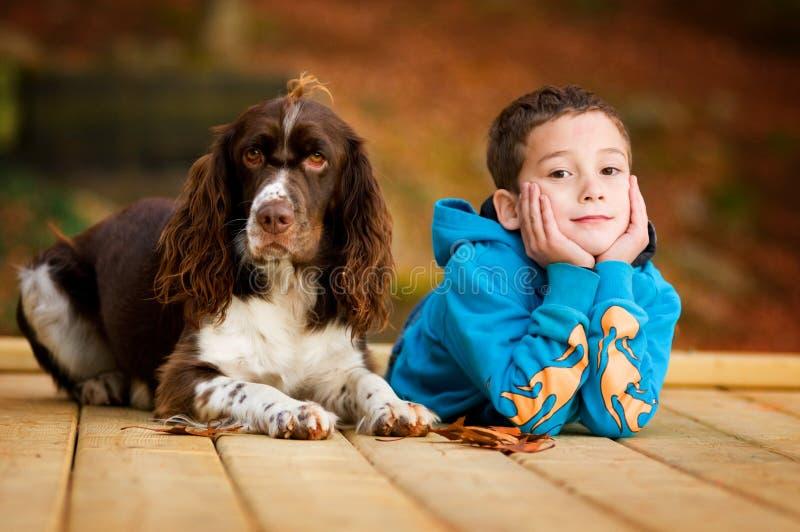 Süßer kleiner Junge und sein Haustierhund lizenzfreie stockbilder