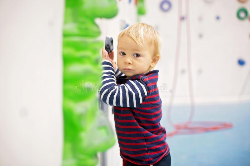 Süßer kleiner Kleinkindjunge, versuchend, Wand zuhause zu klettern stockfotografie