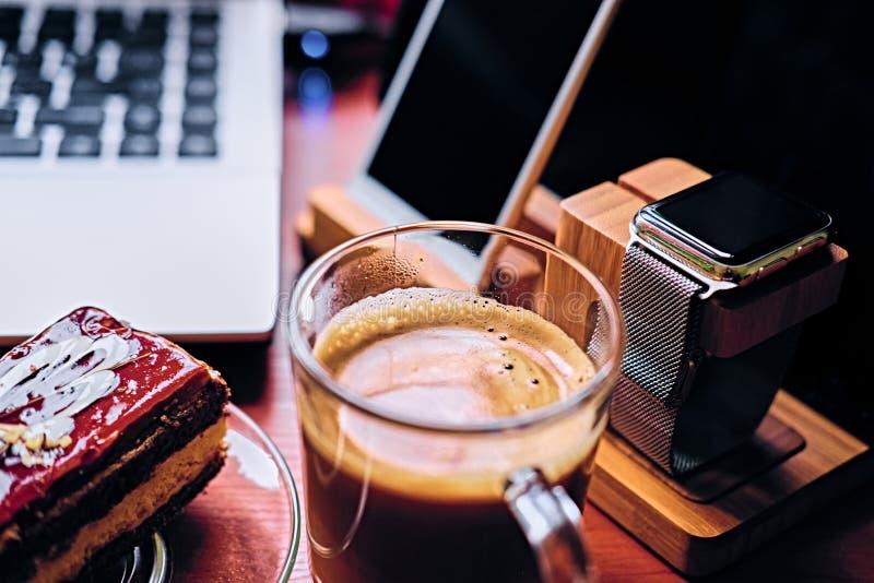 Süßer Kuchen, Tasse Kaffee auf einer Tabelle mit intelligenter Uhr, Laptop lizenzfreies stockbild