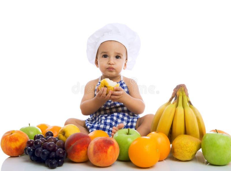 Süßer schöner Babykoch, der gesunde Früchte isst stockbild